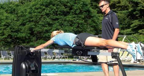 triathlete getting coached on dryland swim bench