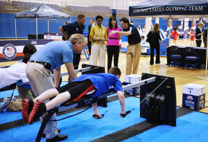 Michelle Obama and Samantha Cameron, wife of British Prime Minister David Cameron, check out USA Swimming's interactive Vasa Ergometer display