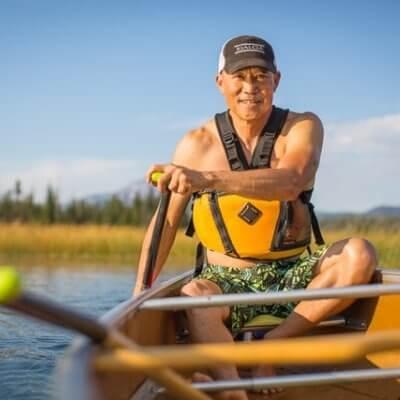 Man paddles canoe on lake