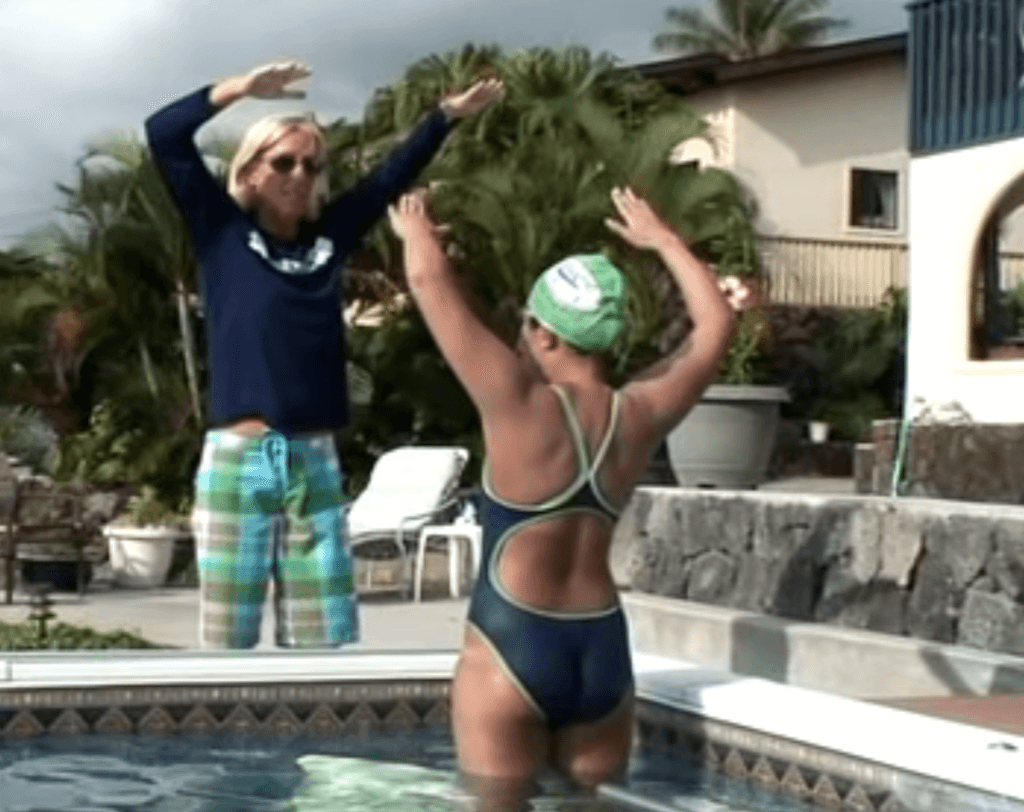 Karlyn teaches high elbow catch poolside for faster freestyle swimming