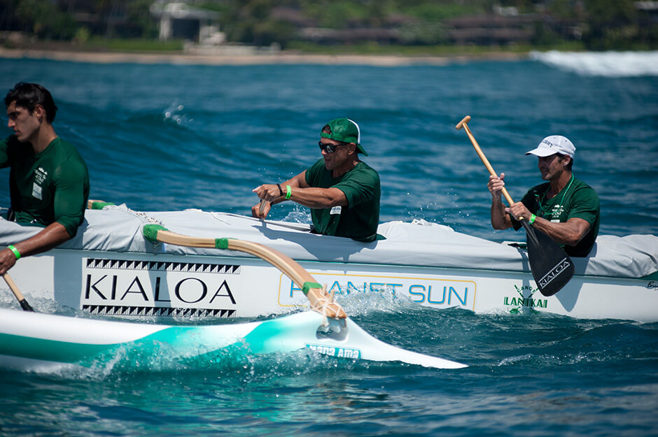 three men race in an outrigger canoe