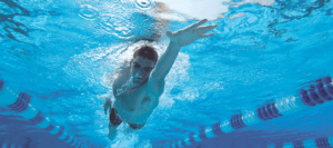 swimmer freestyle in pool reaching out