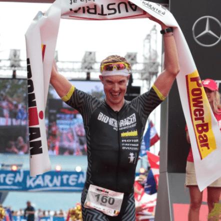 Ironman Sam Gyde winning race holding ribbon