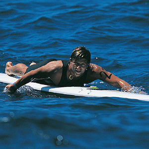 Surfer racing paddleboard